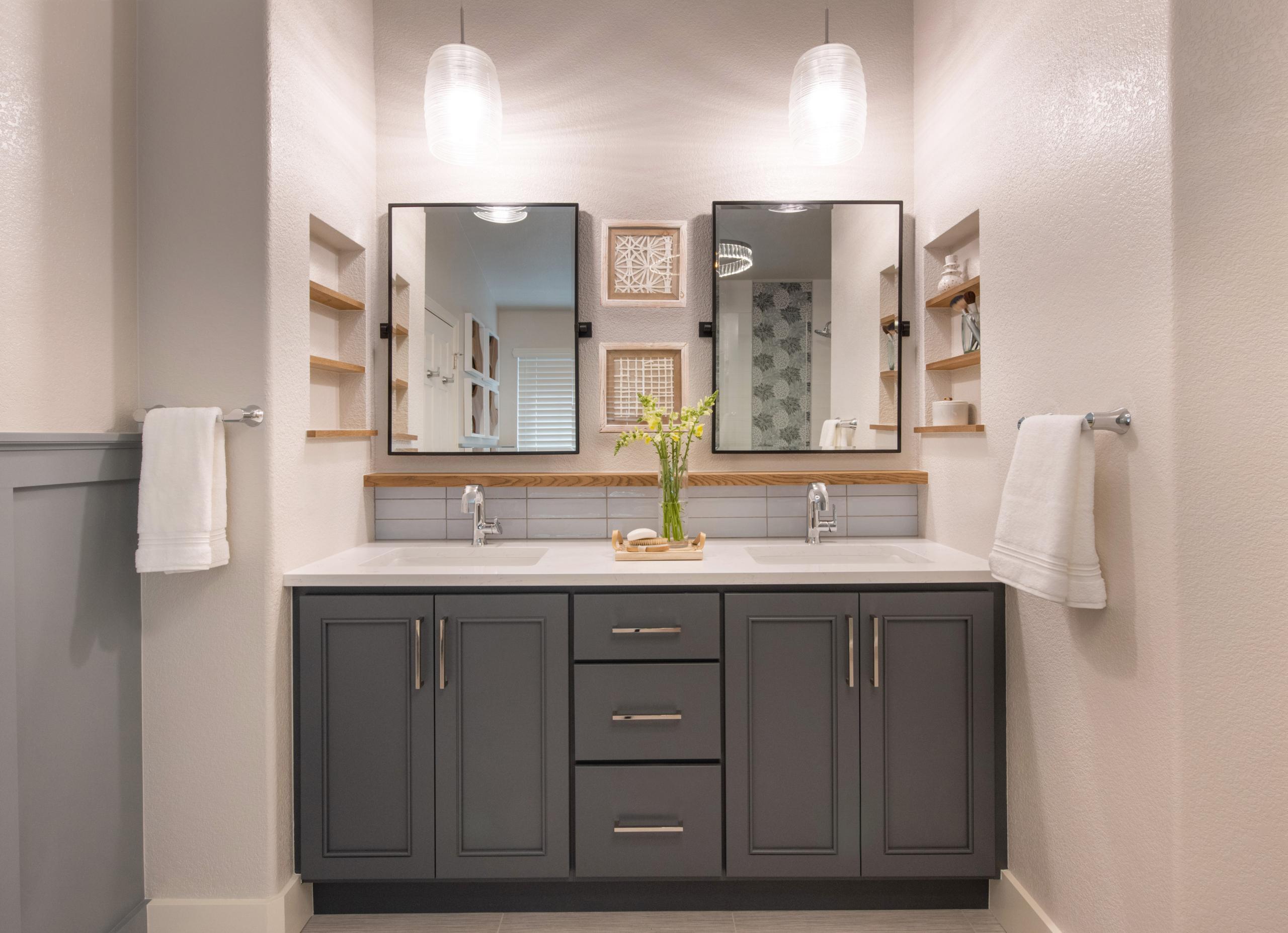Littleton master suite Remodel Master bathroom vanity. Dark blue cabinets, light blue backsplash, light wooden floating shelf and black metal framed mirrors