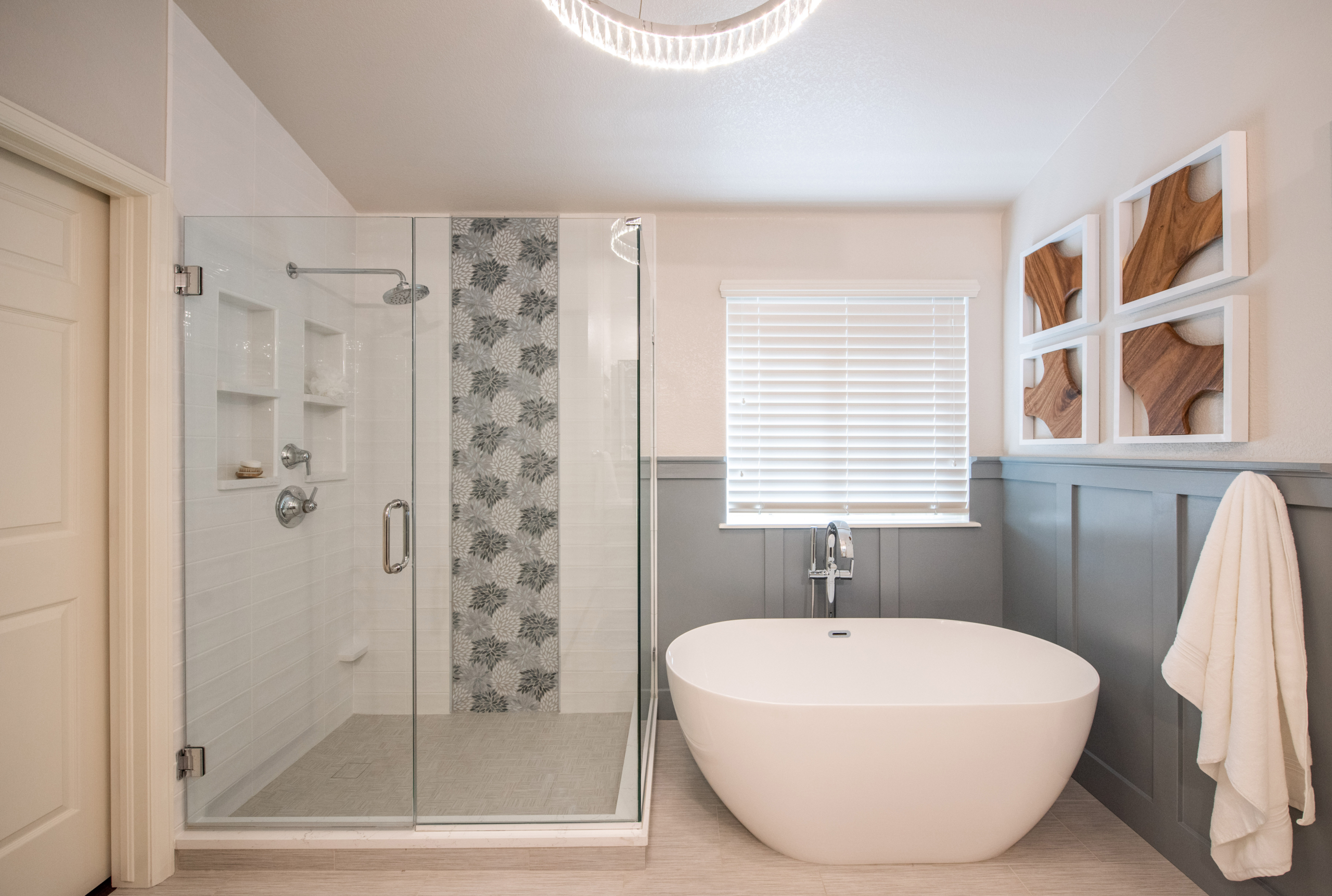 modern glass surround shower in master bath with white subway tile and light blue floral mosaic accent. Next to free standing tub, light blue paneling, wood artwork on walls