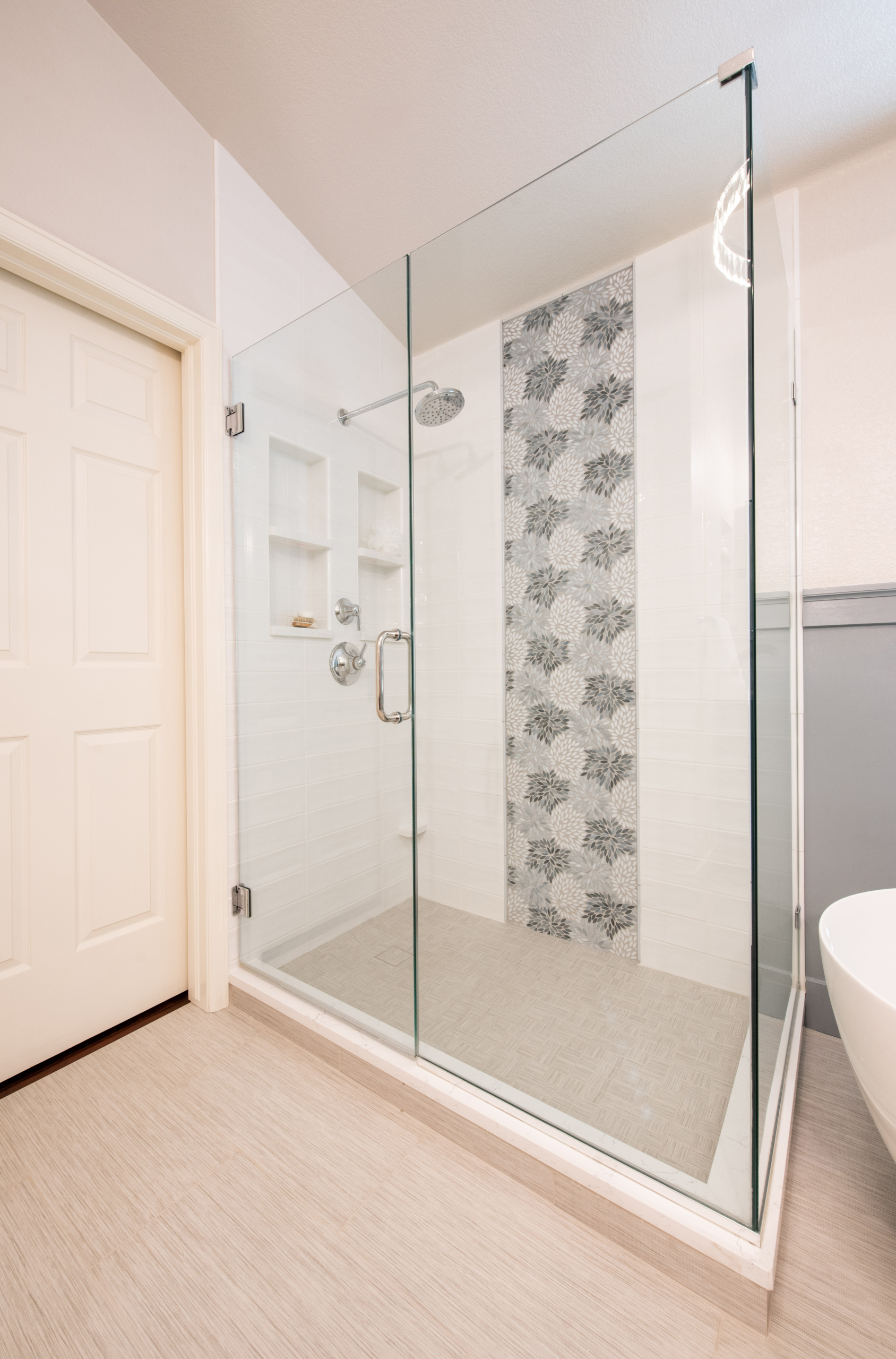 modern glass surround shower in master bath with white subway tile and light blue floral mosaic accent.