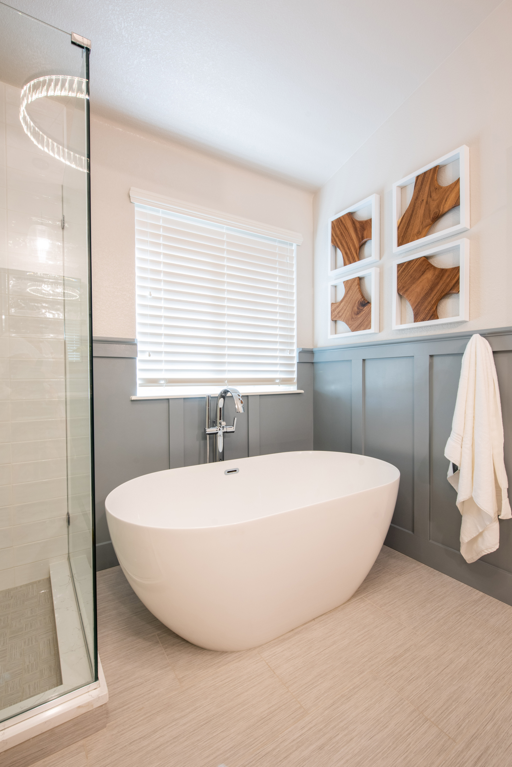 master bathroom with free standing tub, light blue paneling, wood artwork on walls