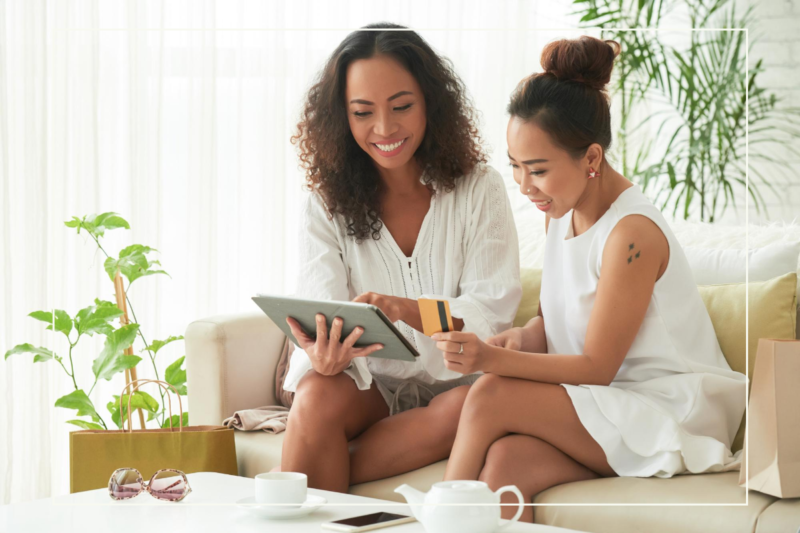 two woman sitting on sofa in light filled room and online shopping with a tablet