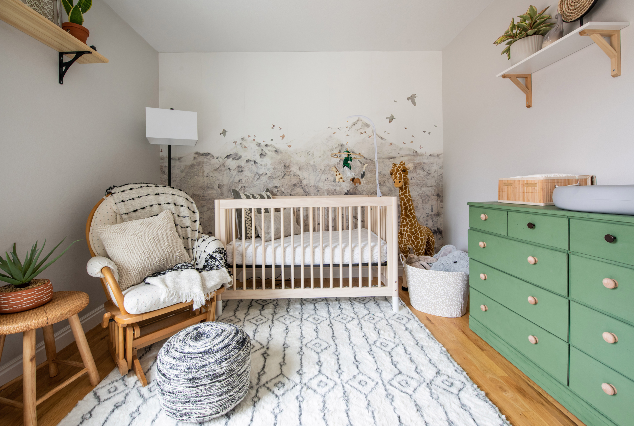 Safari nursery in Louisville CO with green dresser, global accents and mountain wallpaper with birds