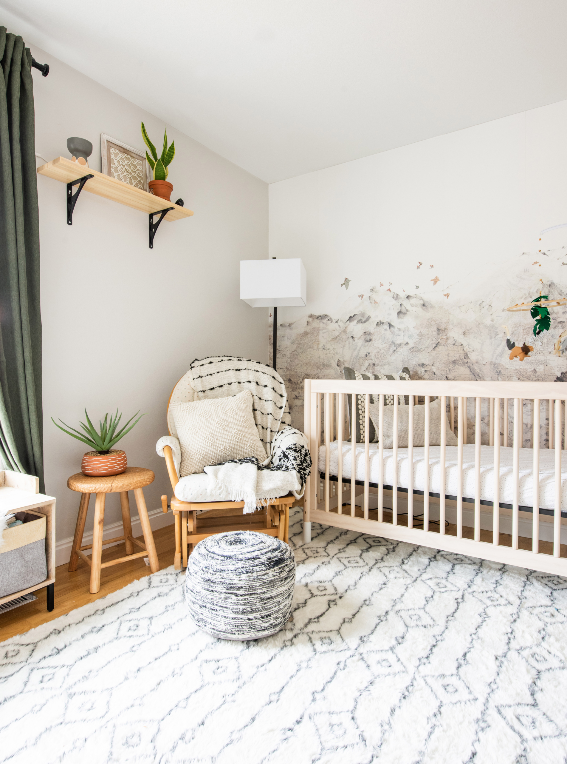 nursery with green curtains white washed crib mountain wallpaper and global accents
