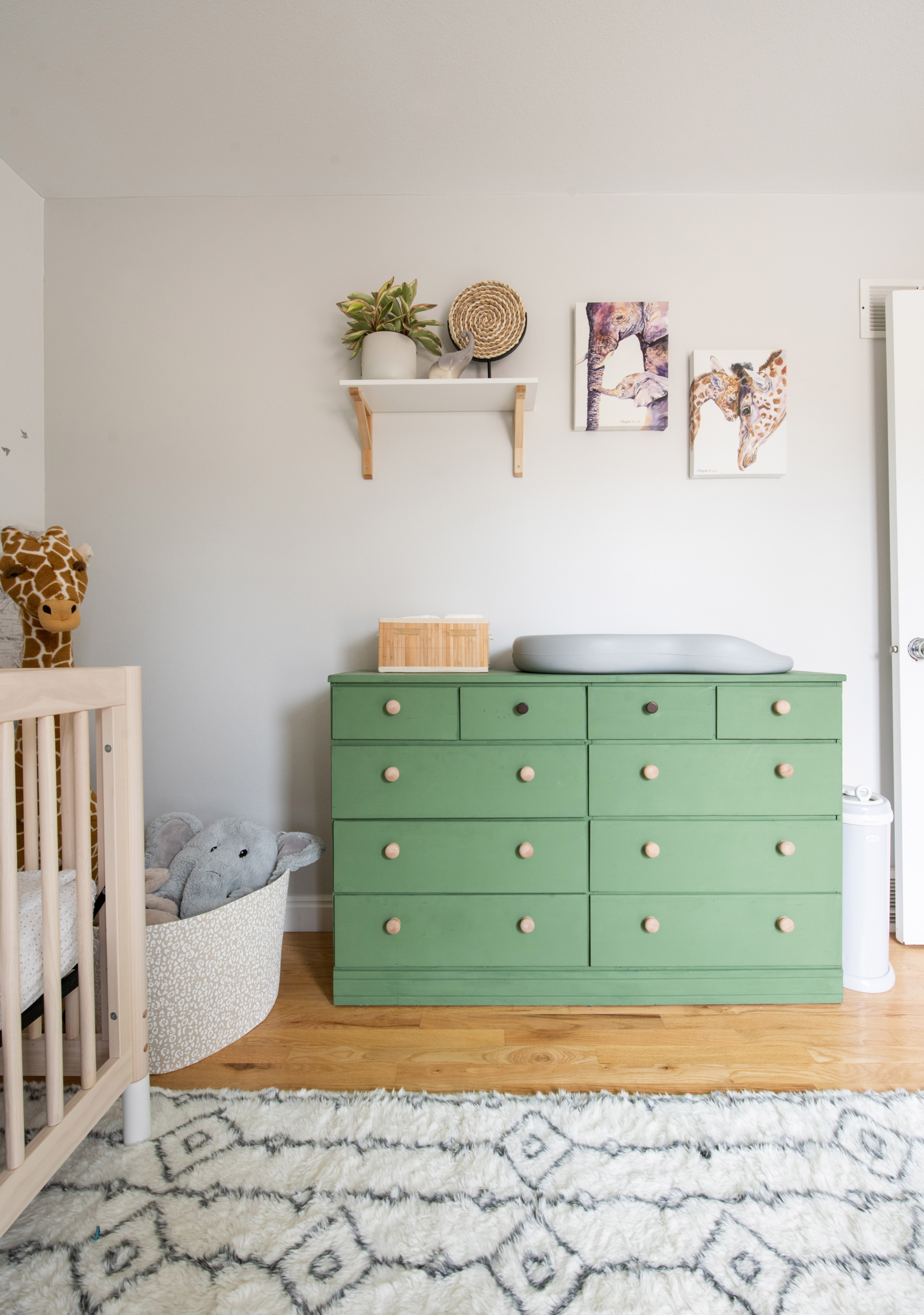 Safari nursery in Louisville CO with green dresser and global accents