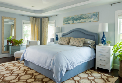 Blue upholstered bed as focal point in serene blue room with geometric rug.