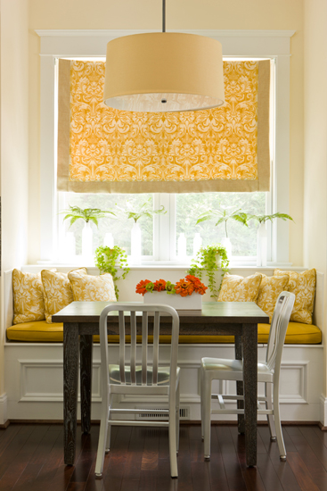 Breakfast room with table and chairs in front of a built-in bench with window above.