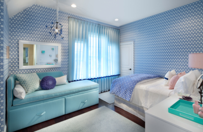 Blue geometric wallpaper with corner chaise by the window.