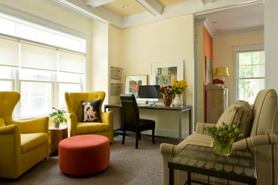 Family room with two mustard chairs in front of window