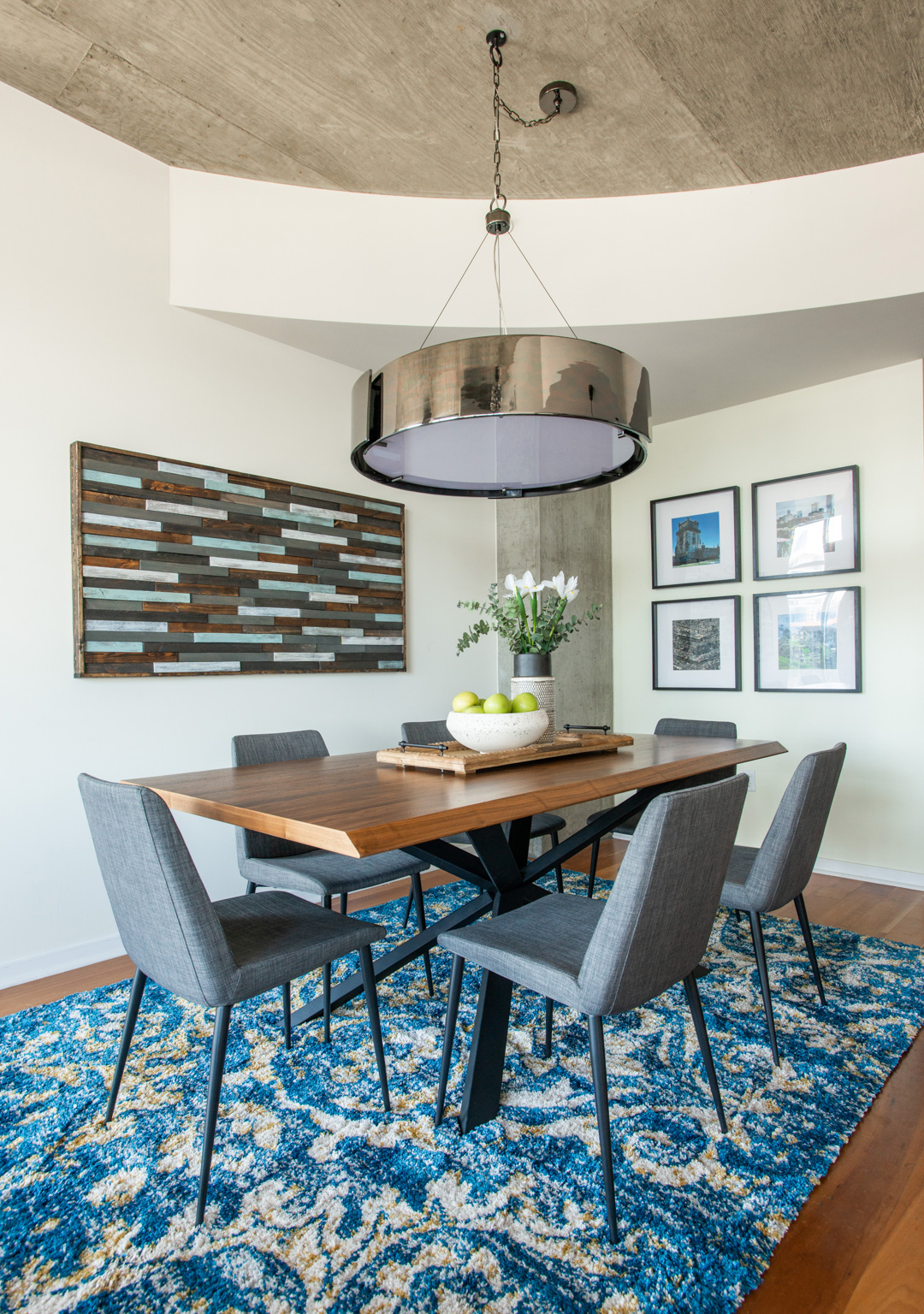 Glass House Condo dining room with table chairs and modern light fixture