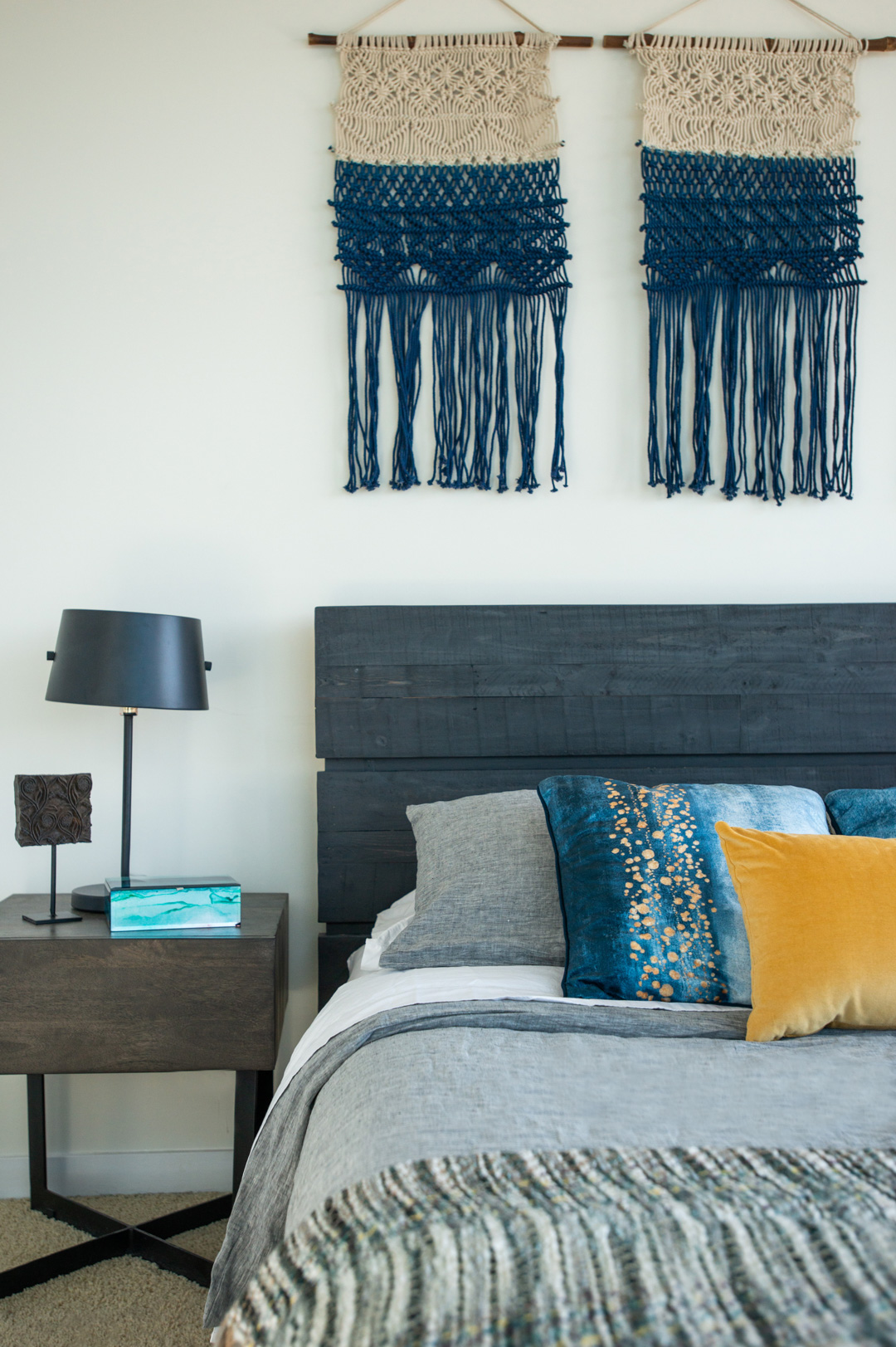 master bedroom bed and nightstand dark wood headboard with blue and yellow pillows