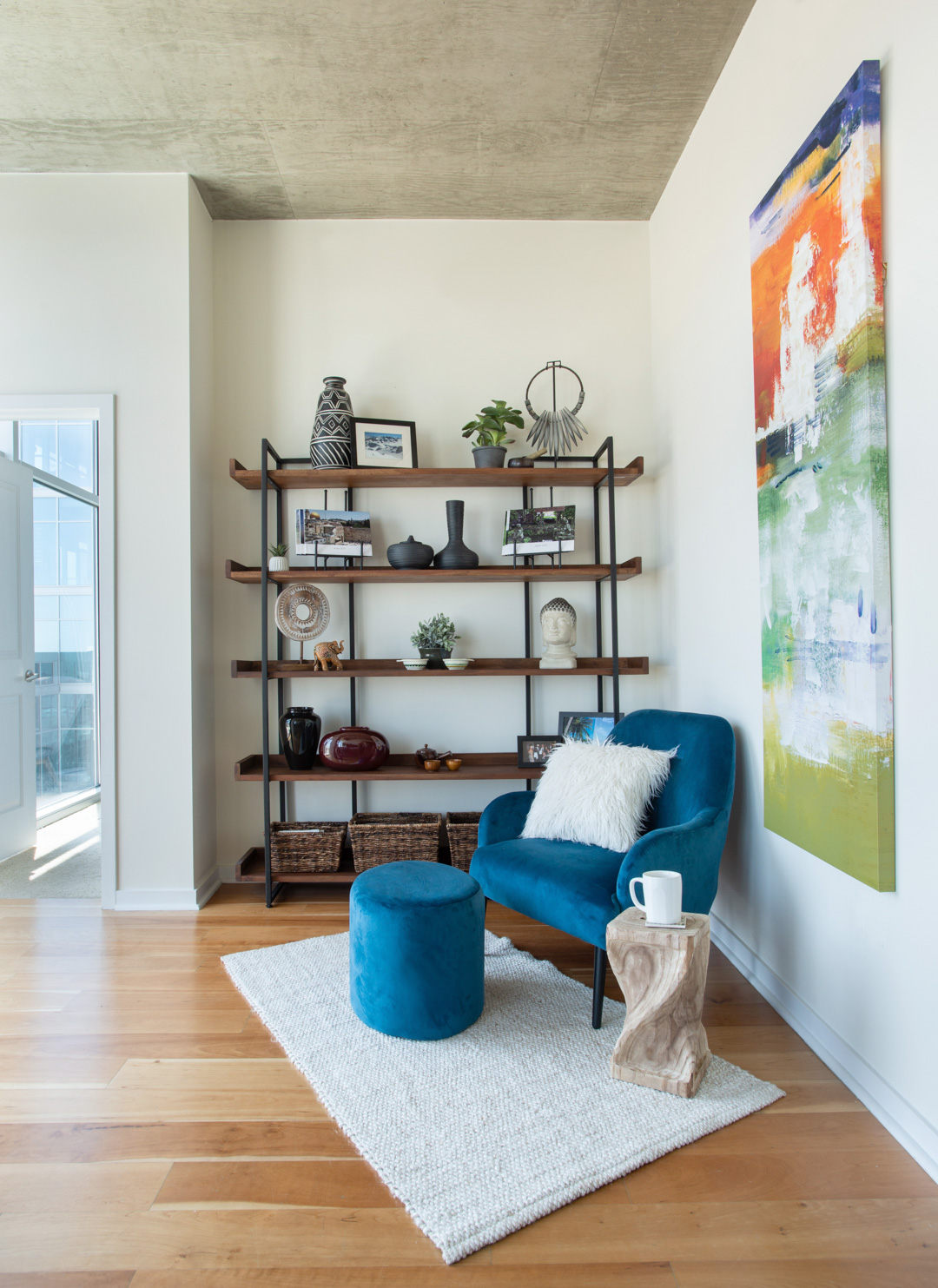 glass house reading nook with blue chair and wooden stool with coffee