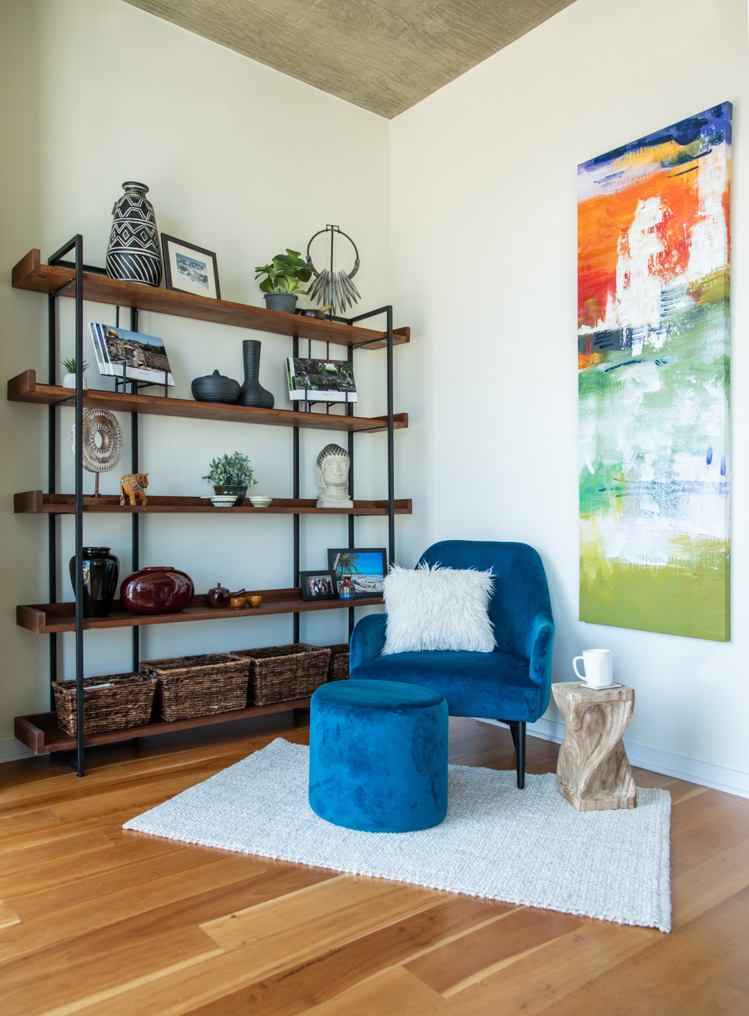 bookcase reading nook with blue velvet chair fuzzy pillow and global decor