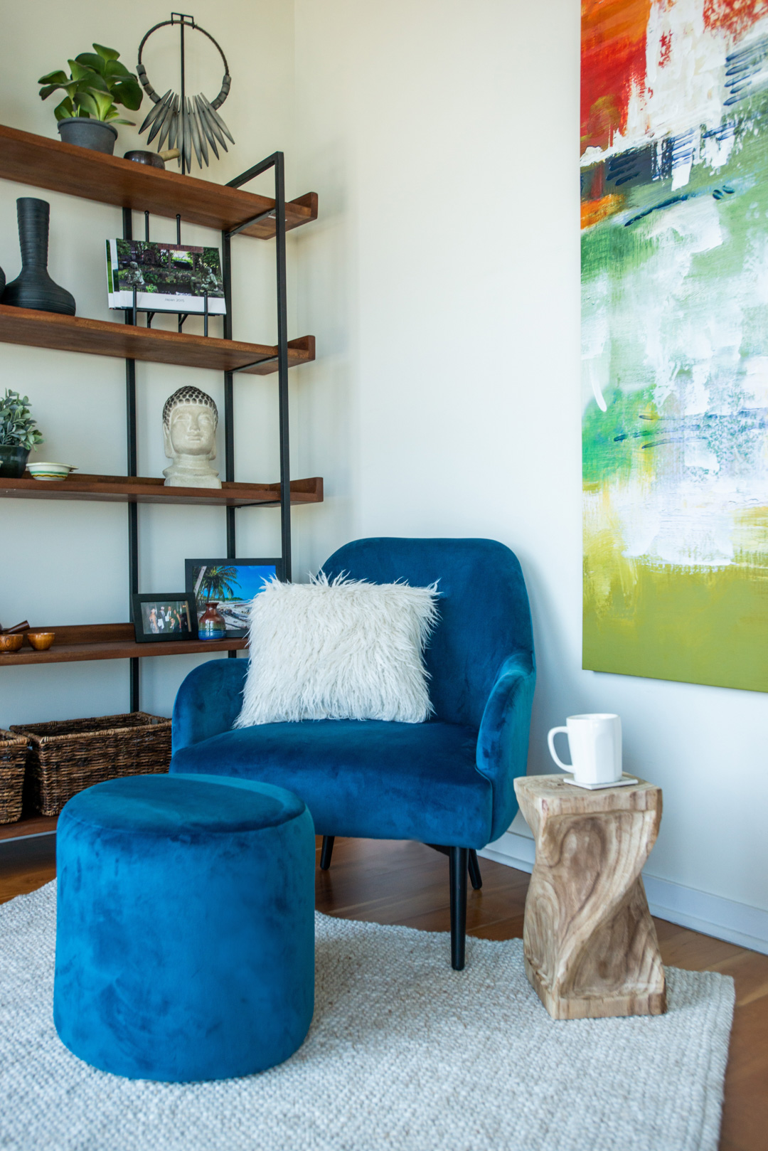 reading nook with blue chair fuzzy pillow and bright abstract art