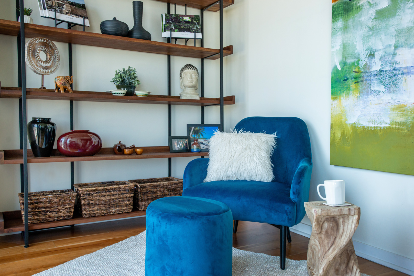 reading nook with bookcase blue chair and abstract art